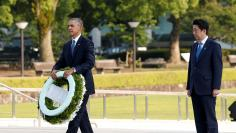 U.S. President Obama carries a wreath as Japanese PM Abe looks on, in front of a cenotaph at Hiroshima Peace Memorial Park in Hiroshima