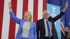 Democratic U.S. presidential candidates Clinton and Sanders stand together during campaign rally in Portsmouth, New Hampshire