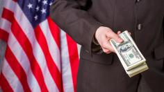 Businessman holding dollars beside flag.