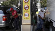 A worker and a customer pump gas into vehicles at a gas station which belongs to PDVSA in Caracas