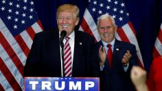 Republican presidential candidate Donald Trump (L) speaks as vice presidential candidiate Mike Pence claps at a post Republican Convention campaign event in Cleveland
