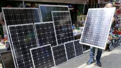 A vendor holds a piece of solar panel to attract buyers at a stall in Manila