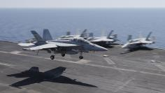 A F/A-18E/F Super Hornets of Strike Fighter Attack Squadron 211 (VFA-211) lands on the flight deck of the USS Theodore Roosevelt (CVN-71) aircraft carrier in the Gulf