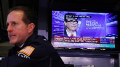 Traders work as a television shows U.S. Treasury Secretary Steven Mnuchin speaking at the New York Stock Exchange as markets continue to react to the coronavirus disease (COVID-19) at the NYSE in New York