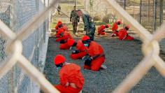 DETAINEES AT CAMP X RAY ARE WATCHED BY US MILITARY POLICE.