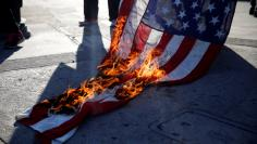 Activists burn a flag while protest on the corner of Florence Ave and Normandie Ave against the police shootings that lead to two deaths in Louisiana and Minnesota, respectively, in Los Angeles, California