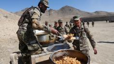 New recruits to the Afghan army Special Forces have their lunch after take part in a military demonstration in Rishkhur district outside Kabul