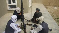 Taliban fighters pose with weapons as they sit in their compound at an undisclosed location in southern Afghanistan in this May 5, 2011 file picture.  REUTERS/Stringer