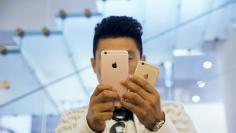 A man uses his phone to take pictures outside an Apple store in Beijing, China July 28, 2016.  REUTERS/Thomas Peter