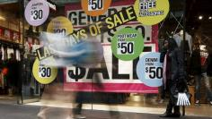 A woman uses her mobile phone in front of sale signs in the window of a clothes store at a shopping mall in central Sydney June 6, 2013.   REUTERS/Daniel Munoz/File Photo
