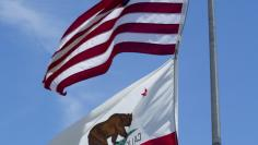 The California and U.S. flags fly in Carson, California, U.S. on August 5, 2015. Picture taken on August 5, 2015.    REUTERS/Mike Blake