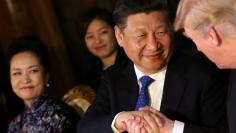 FILE PHOTO: Chinese President Xi Jinping shakes hands with U.S. President Donald Trump as he is accompanied by China's first lady Peng Liyuan during a dinner at the start of a summit between President Trump and President Xi at Trump's Mar-a-Lago estate i