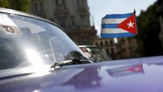 A Cuban flag flies attached on a vintage car in Havana September 18, 2015. REUTERS/Carlos Garcia Rawlins