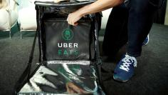 A staff delivers food as he demonstrates a food-delivery service at the launching event of UberEats in Tokyo