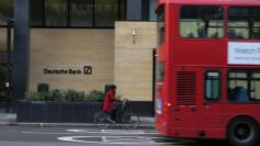 FILE PHOTO: A woman cycles behind a London bus as they pass by a Deutsche Bank building in the City of London