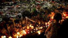 A child stands near flowers and burning candles placed to pay tribute to victims of the truck attack along the Promenade des Anglais on Bastille Day that killed scores and injured as many in Nice, France, July 17, 2016.  REUTERS/Pascal Rossignol