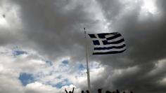 FILE PHOTO: A Greek national flag (R) and a European Union flag flutter atop the Finance Ministry building during sunset in Athens, Greece March 5, 2015. REUTERS/Alkis Konstantinidis/File photo