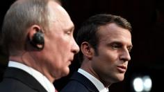 French President Emmanuel Macron (R) and Russian President Vladimir Putin (L) give a joint press conference at the Chateau de Versailles before the opening of an exhibition marking 300 years of diplomatic ties between the two countries in Versailles, Fra