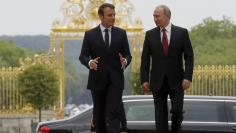 Russian President Putin and French President Macron walk during a meeting at the Chateau de Versailles near Paris