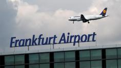Ground staff of Frankfurt airport operator Fraport stand on a ladder in front a Lufthansa Logo at Frankfurt Airport