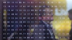 A man walks past a display of hexadecimal code on the Telekom exhibition stand at CeBIT trade fair in Hannover