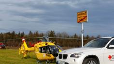 Helicopters of rescue services and an ambulance are seen at a field near Bad Aibling