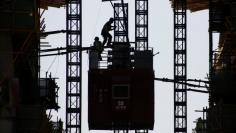 Workers stand on the roof of an elevator at the construction site of a new financial district in Beijing