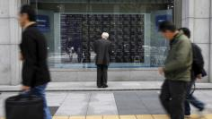 People are reflected in a stock quotation board outside a brokerage in Tokyo, Japan, April 18, 2016.  REUTERS/Toru Hanai