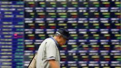 A man walks past an electronic stock quotation board outside a brokerage in Tokyo, Japan, September 22, 2017.   REUTERS/Toru Hanai - RC16074E2450