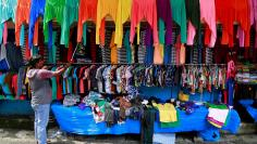 FILE PHOTO: A vendor arranges clothes at his roadside shop in Kochi