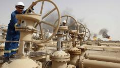 Workers adjust the valves of an oil pipe as smoke rises from burning excess gas in Zubair oilfield in Basra