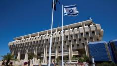 FILE PHOTO: An Israeli flag flutters outside the Bank of Israel building in Jerusalem