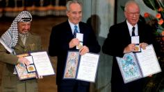 File photo of PLO Chairman Yasser Arafat, Israeli Foreign Minister Shimon Peres and Israeli Prime Minister Yitzhak Rabin showing their shared Nobel Peace Prize in Oslo