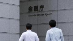 Men walk toward a sign of Japan's Financial Services Agency in Tokyo August 7, 2014. REUTERS/Toru Hanai