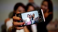 Models pose for photographs with a LG electronics' new V20 premium smartphone during its unveiling ceremony in Seoul