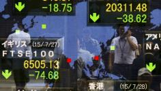 People are reflected in a board showing market indices in Tokyo July 28, 2015.    REUTERS/Thomas Peter