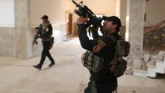 Iraqi special forces soldiers search a building located inside a church compound in Bartella, east of Mosul, Iraq