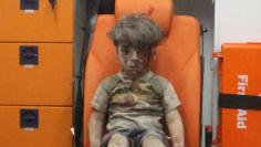 Five-year-old Omran Daqneesh, with bloodied face, sits inside an ambulance after he was rescued following an airstrike in the rebel-held al-Qaterji neighbourhood of Aleppo