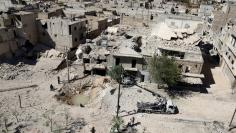 A general view shows a hole in the ground filled with water in a damaged site after airstrikes on the rebel held Tariq al-Bab neighbourhood of Aleppo