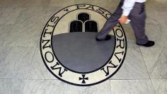 A man walks on a logo of the Monte Dei Paschi Di Siena bank in Rome, Italy September 24, 2013.  REUTERS/Alessandro Bianchi/File Photo