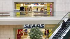 A woman pushes a pushchair past the the Sears department store at Fair Oaks Mall in Fairfax