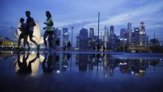 FILE PHOTO - Joggers run past as the skyline of Singapore's financial district is seen in the background April 21, 2014. REUTERS/Edgar Su