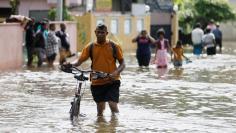 A man pushes his bike through a flooded road in Dodangoda village in Kalutara