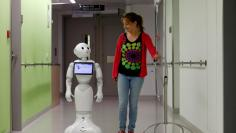"A woman walks with ""Pepper"" the robot at AZ Damiaan hospital in Ostend"