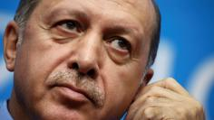 FILE PHOTO: Turkey's President Tayyip Erdogan adjusts earphones during a news conference in Hangzhou