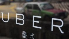 FILE PHOTO -  A taxi is reflected in a window at the office of taxi-hailing service Uber Inc in Hong Kong, China