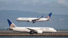 FILE PHOTO: A United Airlines jet taxis as another lands at San Francisco International Airport.   REUTERS/Louis Nastro
