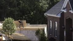 A lone carpenter carries plywood flooring next to a completed home (R) at a building site of Mid-Atlantic Builders' 'The Villages of Savannah' in Brandywine, Maryland May 31, 2013. REUTERS/Gary Cameron
