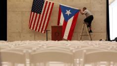 A worker takes off U.S and Puerto Rican flag in San Juan, Puerto Rico, May 16, 2016. REUTERS/Alvin Baez