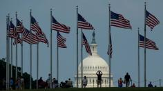 Flags fly at the Washington Monument as the U.S. Capitol is seen at rear on Flag Day in Washington